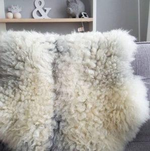 Grijze schapenvacht van Sheepy over bankleuning.